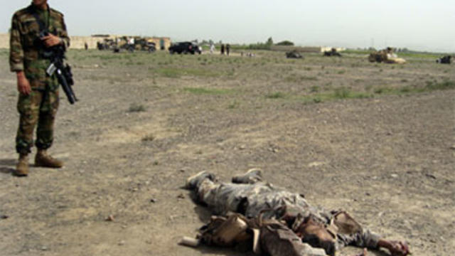 An Afghan National Army soldier stands near the body of a suicide attacker near a NATO base in Khost province of Afghanistan, Saturday, Aug. 28, 2010.
