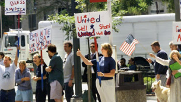 A gathering of well-wishers wave patriotic signs and shout encouragement as President Bush and his motorcade depart a prayer service at the National Cathedral in Washington, Friday, Sept. 14, 2001.