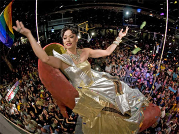"""Sushi,"" portrayed by female impersonator Gary Marion, dangles high above New Year's Eve revelers in a giant reproduction of a woman's high heel at the Bourbon Street Pub late Friday, Dec. 31, 2010, in Key West, Fla."