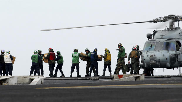 sailors move food and water onto an HH-60H Sea Hawk
