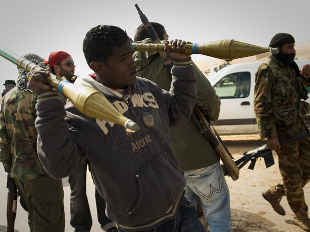 A Libyan rebel carries rockets
