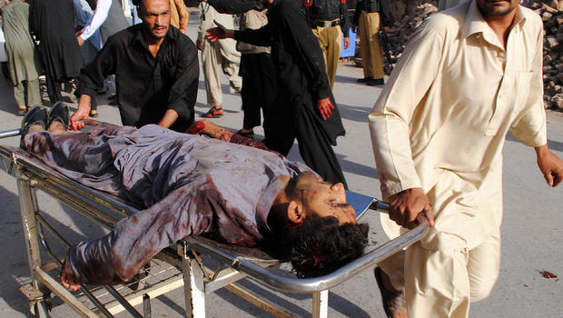 An injured man is rushed to a local hospital in Peshawar after a bombing