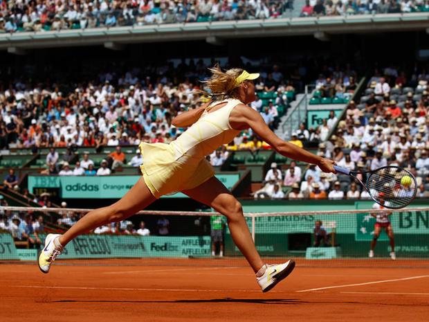 Maria Sharapova returns the ball to China's Li Na