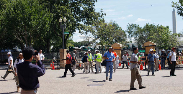Office and construction workers at the White House complex cross Pennsylvania Ave. in Washington, Aug. 23, 2011, after buildings where evacuated following an earthquake in the Washington area.