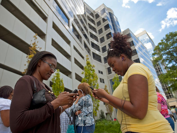 Blue Cross Blue Shield employees Keonna Freeman, left, 28, and Erica Cole, 33, check their mobile devices after a 5.8 magnitude earthquake in central Virginia sent tremors up the east coast, Aug. 23, 2011, in downtown Wilmington, Del.