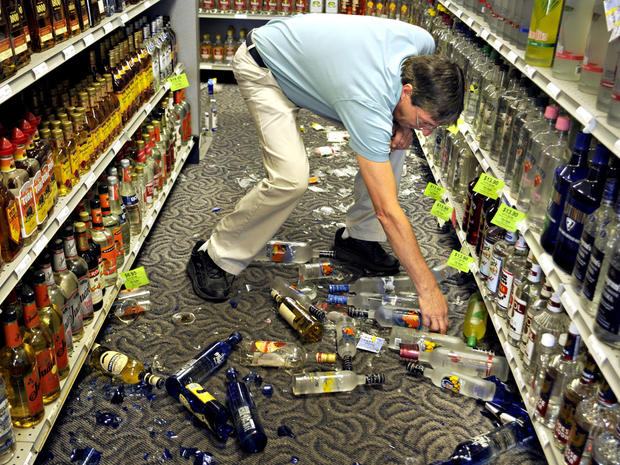 Ben Gayle picks up broken glass and liquor bottles after an earthquake shook the ABC Store on Route 218 in Stafford, Va.