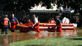 Rescue workers pull a boat with a woman as they wade through floodwaters caused by Hurricane Irene, Aug. 29, 2011, Pompton Lakes, N.J.