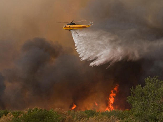Helicopter drops water on a wildfire near Possum Kingdom Lake, Texas