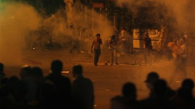 Protesters throw stones as tear gas is seen around them during clashes with Egyptian security forces next to building housing the Israeli embassy in Cairo early Saturday
