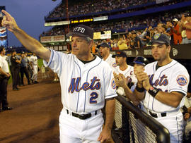 New York Mets manager Bobby Valentine, wearing a New York Police Department cap, and catcher Mike Piazza, wearing a Port Authority Police Department cap, applaud in honor of New York City Mayor Rudy Giuliani before a baseball game against the Atlanta Braves Sept. 21, 2001, at Shea Stadium in Flushing, N.Y. The Mets won 3-2.