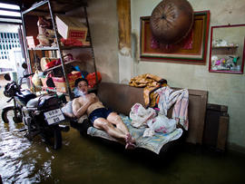A Thai resident watches television in his flooded home in Chinatown near the overflowing Chao Phraya river Oct. 26, 2011, in Bangkok. Floodwaters are threatening to disrupt Thailand's tourism industry as the country experiences its worst flooding in 50 years.