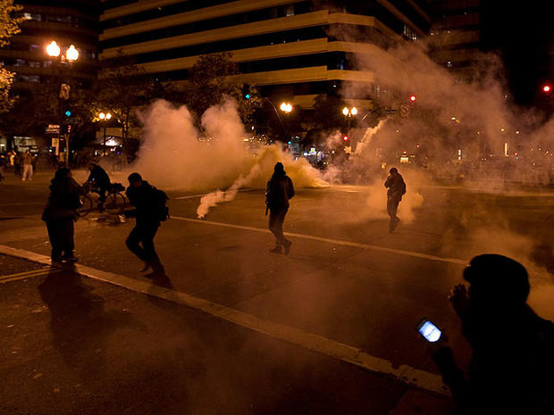 Occupy Wall Street protesters run from tear gas deployed by police at 14th Street and Broadway in Oakland, Calif., Oct. 25, 2011.