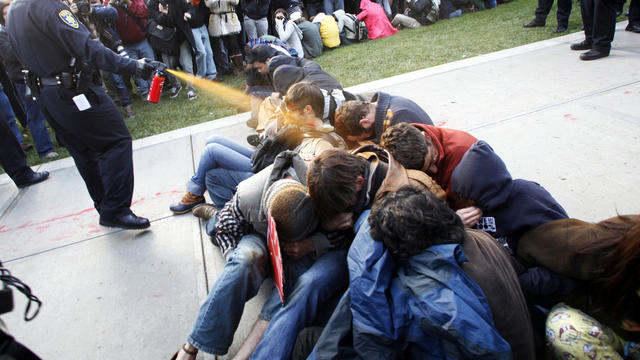 University of California, Davis, Police Lt. John Pike uses pepper spray to move Occupy UC Davis protesters while blocking their exit from the school's quad Nov. 18, 2011, in Davis, Calif. Two officers involved in pepper spraying seated protesters were pla
