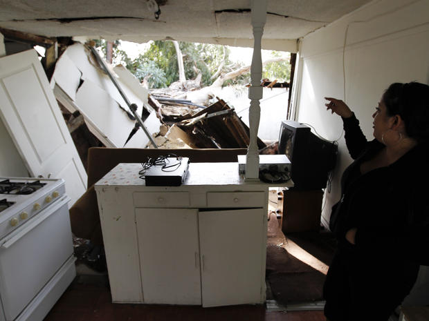 Crystal Walters looks at the wind damage to her home