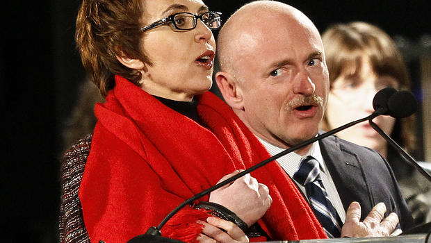 Rep. Gabrielle Giffords leads the Pledge of Allegiance accompanied by her husband, former astronaut Mark Kelly, Jan. 8, 2012, in Tucson, Ariz., at the start of a memorial vigil remembering the victims and survivors one year after the Arizona congresswoman