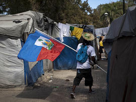 A demonstrator waves a Haitian flag while walking between makeshift tents at the temporary camp in Champ de Mars, across the street from the collapsed National Palace, during a protest to demand new housing in Port-au-Prince, Haiti, Jan. 11, 2012.