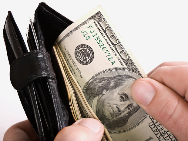 Man holding a wallet with cash in it.