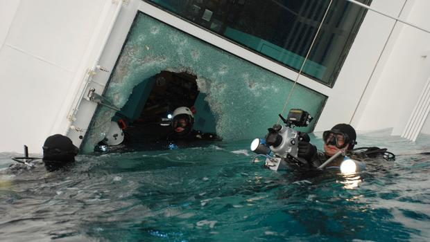 Italian scuba divers swim around the wreck of the Costa Concordia