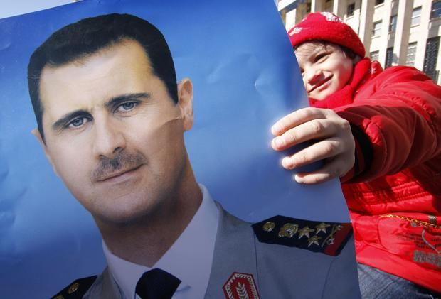 Pro-Syrian regime protester holds a portrait of Syrian President Bashar Assad