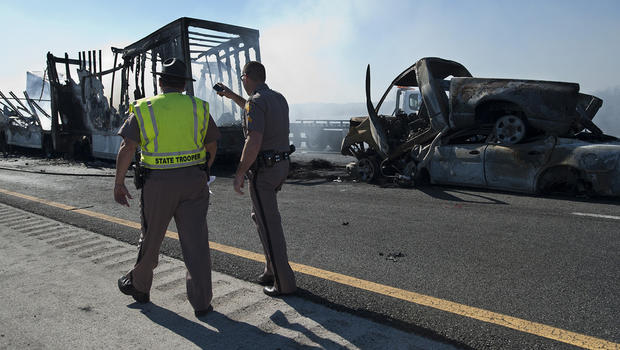 Florida Highway Patrolmen inspect the damage from a multi-vehicle accident