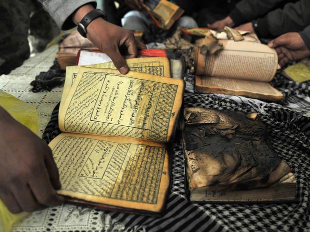 Afghan demonstrators show copies of Koran books allegedly set alight by U.S. soldiers.