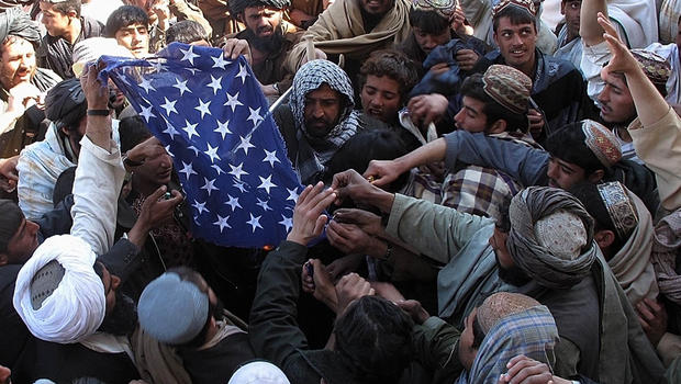 Afghan demonstrators destroy a U.S. flag