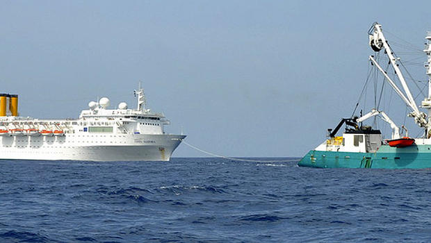 In this photo taken by a member of French fishing vessel, The Talenduic, and provided by the Prefecture of the Reunion Island, shows the Italian cruise ship, The Costa Allegra, left, being towed by French fishing vessel, The Trevignon, in the Indian Ocean