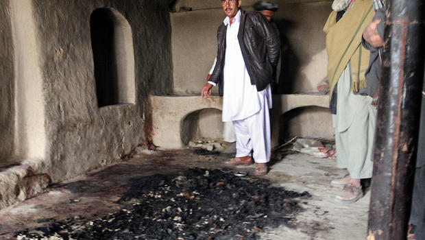Men stand next to blood stains and charred remains inside a home where witnesses say Afghans were killed by a U.S. soldier