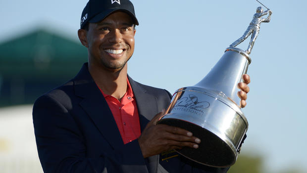Tiger Woods hoists the championship trophy after winning the Arnold Palmer Invitational