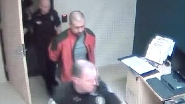 Still from video from inside Sanford, Fla. police station shows a handcuffed George Zimmerman being led by police