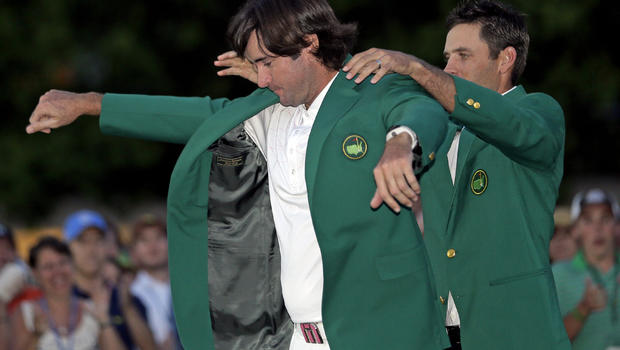 Charl Schwartzel, right, of South Africa, helps Bubba Watson put on the green jacket after winning the Masters golf tournament