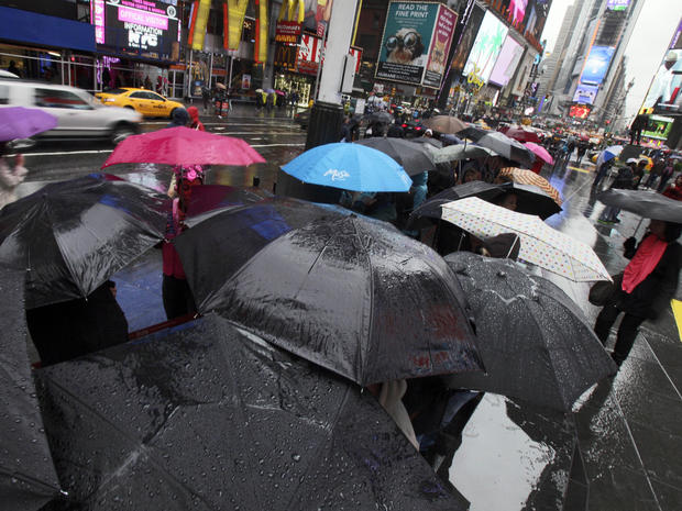 Umbrellas shelter people waiting to buy Broadway theater tickets in New York's Times Square, Sunday as leading edge of nor'easter hits on April 22, 2012