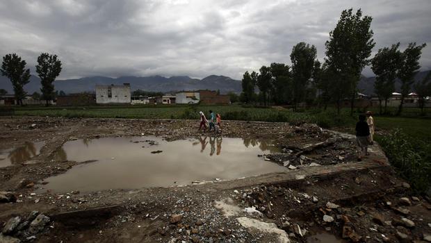 Pakistani girls walk at the demolished compound of Osama bin Laden, in Abbottabad, Pakistan