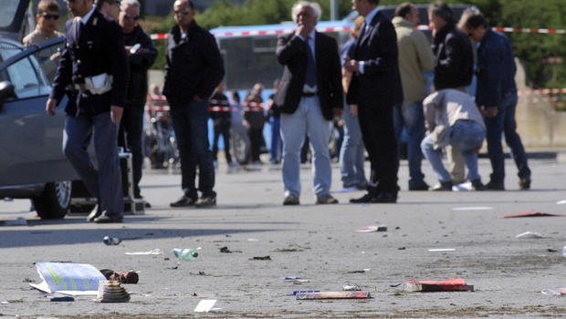 "Italian policemen, background left, walk on site where explosive device went off outside ""Francesca Morvillo Falcone"" high school in Brindisi, Italy, Saturday"
