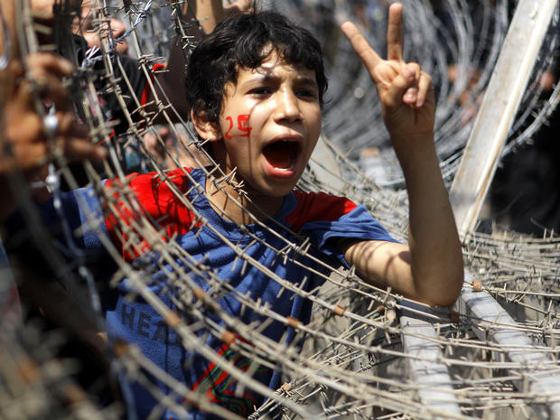 An Egyptian boy peers out of barbed wire, his face painted with the number 25, the date of the Egyptian revolution, during a protest in front of the Supreme Constitutional Court in Cairo June 14, 2012.