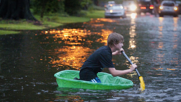 Mac Lyerly, 12, of Jacksonville, smiles as he paddles a small plastic swimming pool down Avondale Avenue as rain totals continue to rise as North Florida residents deal with the ongoing rains from Tropical Storm Debby Tuesday June 26, 2012.