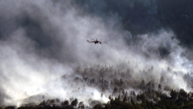 A helicopter flies over the Waldo Canyon fire as it continues to burn June 27, 2012, in Colorado Springs, Colo.