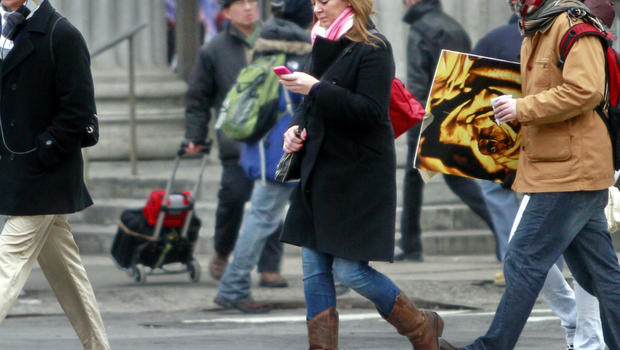 A pedestrian looks at her cell phone while crossing the street in New York City.