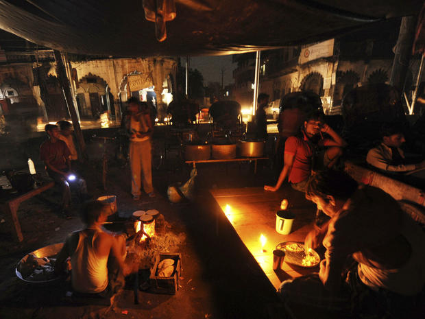 An Indian man prepares a meal as others sit at a roadside shop on a dark street following a power outage near a railway station in Allahabad, India, Tuesday, July 31, 2012.