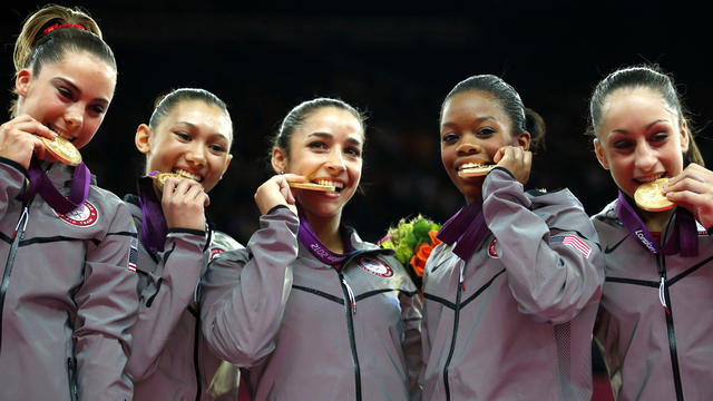 U.S. gymnasts McKayla Maroney, Kyla Ross, Alexandra Raisman, Gabrielle Douglas and Jordyn Wieber bite their gold medals at the artistic gymnastics women's team final at the 2012 Summer Olympics July 31, 2012, in London.