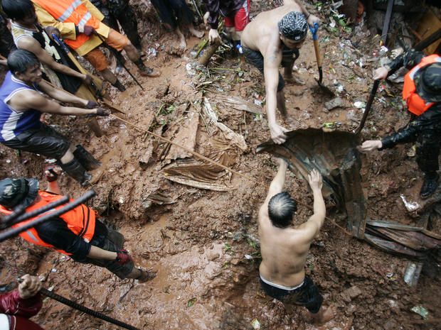 Filipino rescuers dig for survivors where four homes collapsed in a landslide