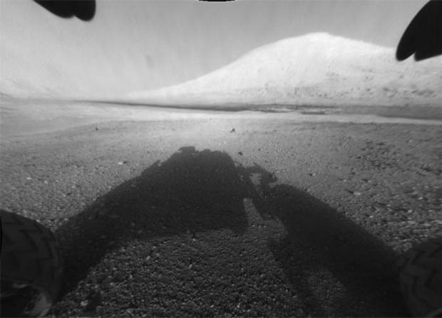 This image taken by NASA's Curiosity shows what lies ahead for the rover -- its main science target, informally called Mount Sharp Monday, Aug. 6, 2012. The rover's shadow can be seen in the foreground, and the dark bands beyond are dunes. Rising up in th