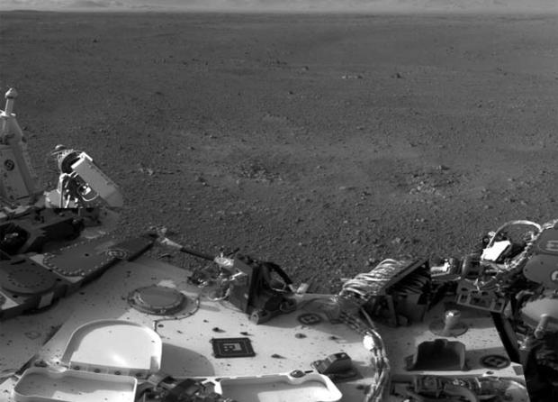 This mosaic image shows part of the left side of NASA's Curiosity rover and two blast marks from the descent stage's rocket engines. The images that were used to make the mosaic were obtained by the rover's Navigation cameras