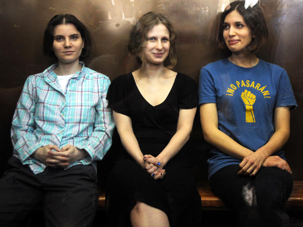 Members of the all-girl punk band Pussy Riot Yekaterina Samutsevich, left, Maria Alyokhina, center, and Nadezhda Tolokonnikova sit in a glass-walled cage during a court hearing in Moscow Aug. 17, 2012.