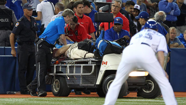 Paramedics stop the game to try and revive a man of an apparent heart attack during MLB action