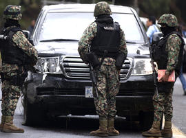 Military guards stand in front of an armored U.S. Embassy vehicle attacked by unknown assailants on the highway leading to the city of Cuernavaca, near Tres Marias, Mexico, Friday, Aug. 24, 2012.