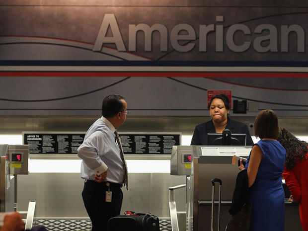 An American Airlines employee helps travelers at the ticket counter in the Miami International Airport on September 18, 2012 in Miami, Florida. Nearly 10 months after the airline filed for bankruptcy protection, the company announced that it will be sending out layoff warning notices to more than 11,000 employees although it expects job losses to be less than that.