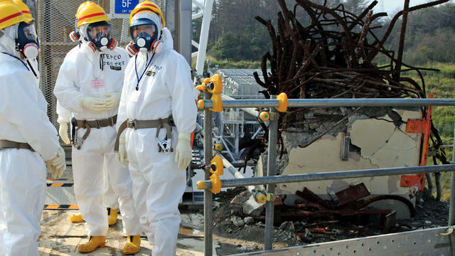 Clad in a protective outfit, Japanese Prime Minister Yoshihiko Noda, right, stands on the rooftop of the Unit 4 reactor building during his inspection of the crippled Fukushima Dai-ichi nuclear power plant in Okuma, Japan, Oct. 7, 2012.