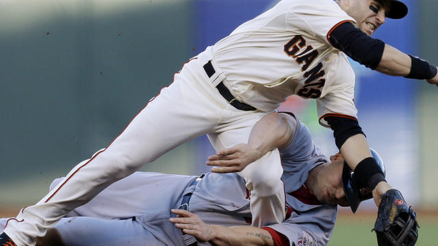 San Francisco Giants second baseman Marco Scutaro grimaces as his leg is caught under a sliding St. Louis Cardinals' Matt Holliday on a double play attempt during the first inning of Game 2 of baseball's National League championship series Monday, Oct. 15