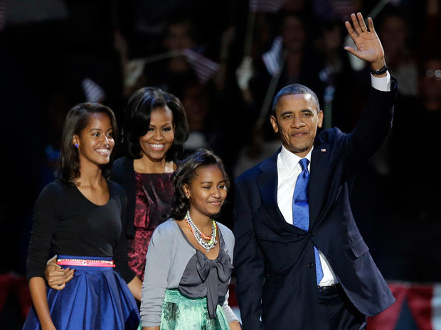 President Barack Obama waves as he walks on stage with first lady Michelle Obama and daughters Malia and Sash